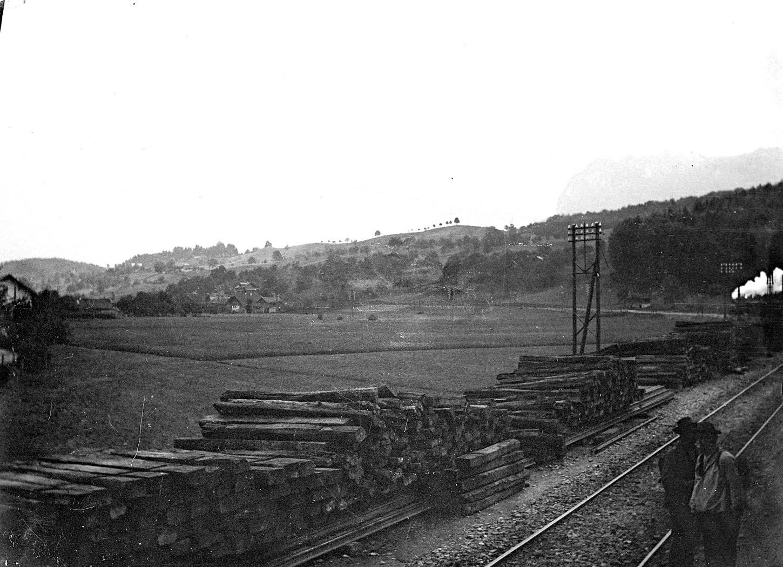 Environs de Berne (Suisse). Travaux sur une voie ferrée : averses en bois entreposées le long d'une voie. Au fond à droite, un train à vapeur. Au second plan, un paysage de montagne