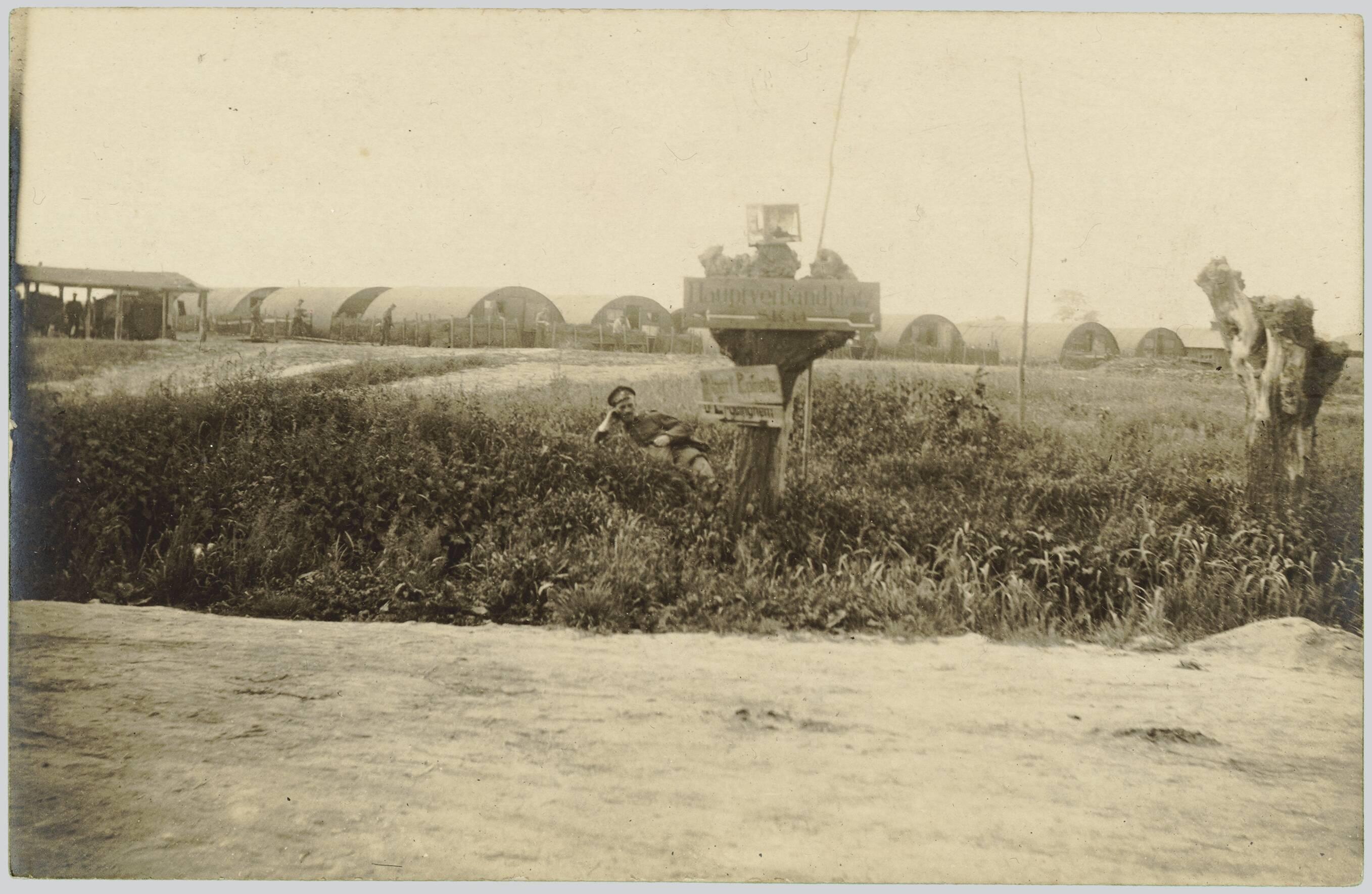 CARTE-PHOTO MONTRANT UN SOLDAT ALLEMAND ALLONGE EN BORDURE D'UN CHEMIN. CAMP D'AVIATION EN ARRIERE PLAN